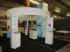 Custom Gravitee One-Step Island Exhibit with Tower, Full-size Closet, TF-1001 Aero Circle Sign, (4) Workstations with Backlit Graphics, Monitor Mounts, and GOD-1560 Reception Counter